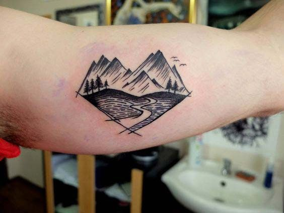 mountains inner bicep tattoo for men