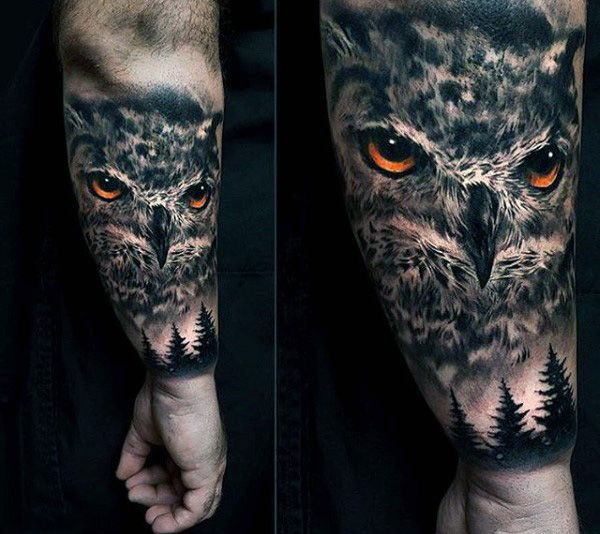 owl face above pine trees men's lower arm tattoo