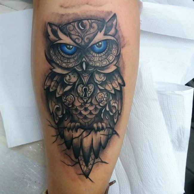 owl with lock design men's arm tattoo