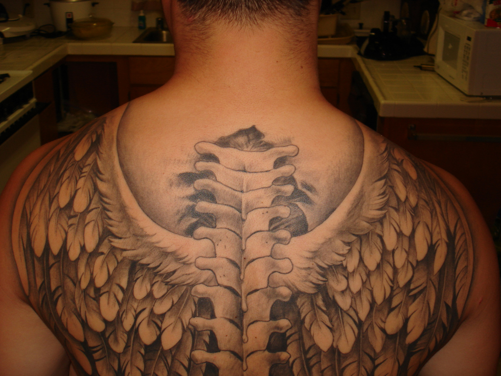 spinal cord and wings tattoo for men