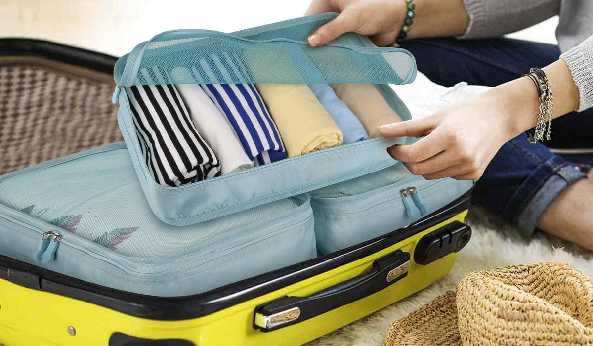 blue packing cubes in a yellow suitcase
